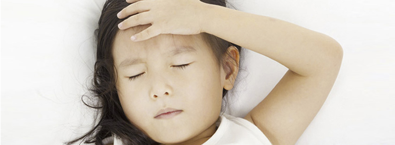 Girl with fever touching her forehead while lying down