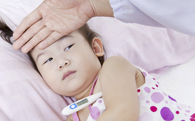 Girl with fever lying in bed with someone's hand on her forehead